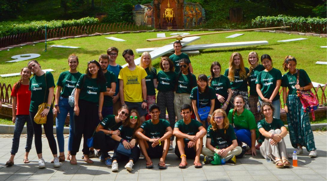 A team of volunteers take a group photo outside Wat Phnom in Cambodia.